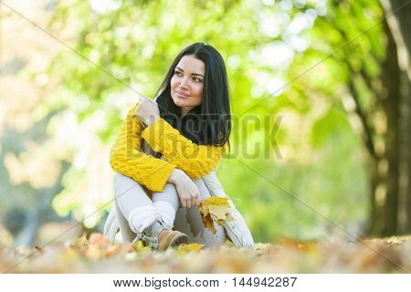 Happy woman sitting on dry leaves in autumn park at sunny day