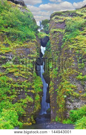 Abounding scenic waterfall inside a cave near Selyalandfoss. Iceland, July