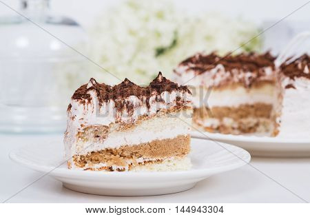 Creamy cake on plate on table on light background