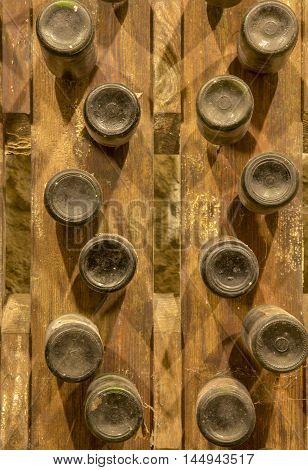 Red wine bottles stacked on wooden racks. Bottom