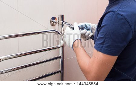 Plumber fixing chrome heated towel rail in bathroom.-