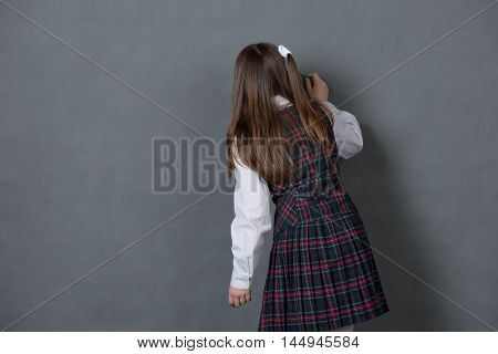Girl in school uniform writing on the chalkboard standing with her back to us