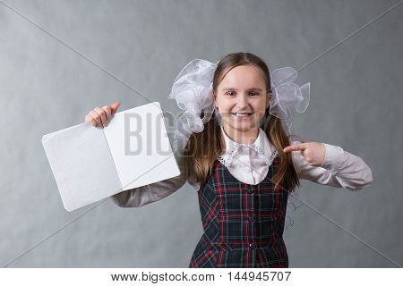 Girl in school uniform and white bows in her hair holding an open notebook