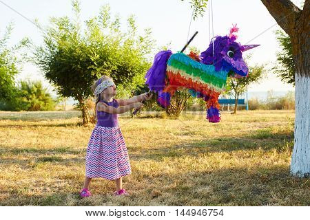 Young girl at an outdoor party hitting a pinata. Celebrating a birthday.