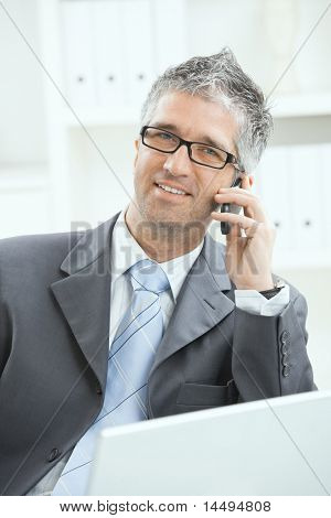 Portrait of businessman wearing gray suit  talking on mobile phone at office. ?