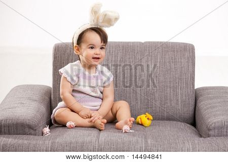 Baby girl in easter bunny costume, sitting on grey couch playing with toy chicken and easter eggs, laughing. Isolated on white background.?