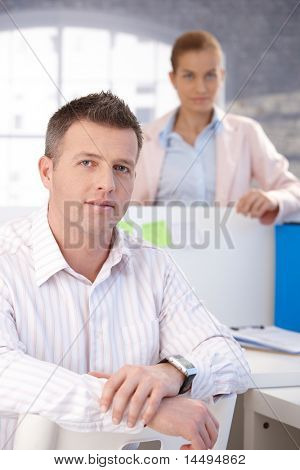 Porträt des mittleren Alters Büroangestellter sitzt am Schreibtisch, Lächeln, Frau, im Hintergrund stehend.?