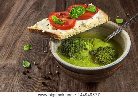 green broccoli vegetable soup and bread with gorgonzola and tomatoes on a rustic wooden table homemade vegetarian meal selected focus and narrow depth of field