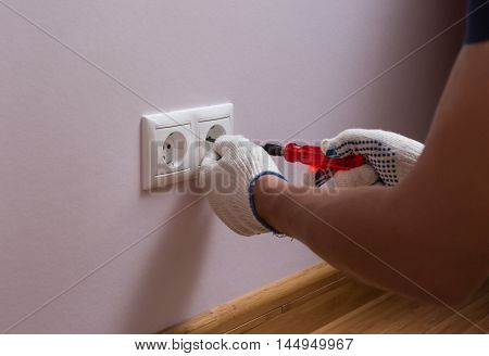 Electrician installing a wall power socket, close up photo.