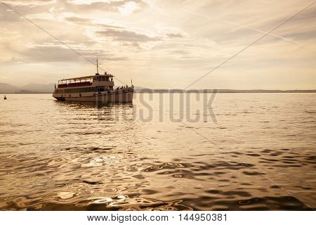 White ferry on Lake Garda at sunset.