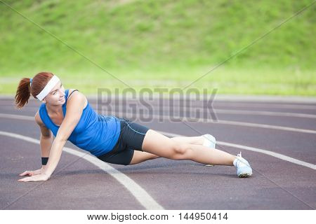 Caucasian Sportswoman in Professional Sportsgear Having Body Stretching Exercises On Sport Venue Outdoors. Horizontal Image