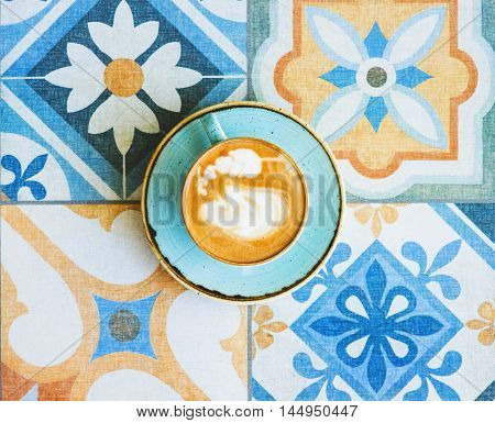 Blue cup of coffee on a stylish tile