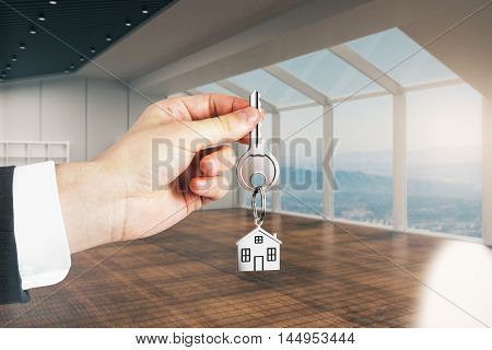 Closeup of businessman hand holding key with house keychain in modern interior. Mortgage concept