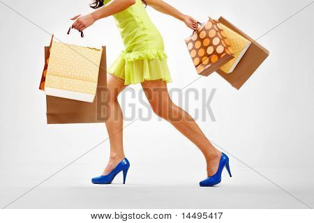 Legs of lady with colorful paper bags in move