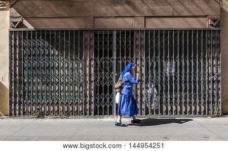 AIX EN PROVENCE FRANCE - AUG 19 2016: nun in blue frock hurries in the midday heat along the footpath. She belongs to the monastery of Aix en Provence.