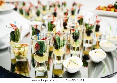 Berry dessert in shot glasses on banquet table, toned image