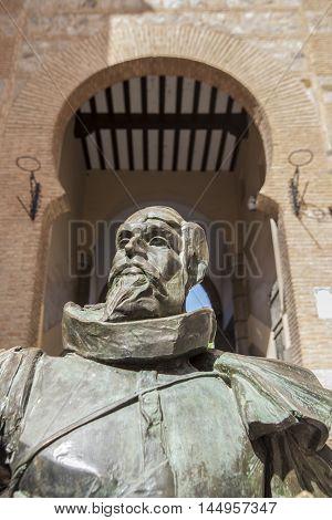 Toledo Spain - July 28 2016: statue of the writer Cervantes located next to Arco de la Sangre arabic door Toledo Spain