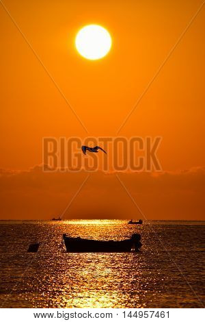 Red sunset with silhouette of boat, South Italy.