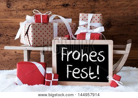 Chalkboard With German Text Frohes Fest Means Merry Christmas. Sled With Christmas And Winter Decoration. Gifts And Presents On Snow With Wooden Background.