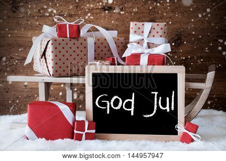 Chalkboard With Swedish Text God Jul Means Merry Christmas. Sled With Christmas And Winter Decoration And Snowflakes. Gifts And Presents On Snow With Wooden Background.