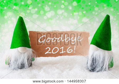 Christmas Greeting Card With Two Green Gnomes. Sparkling Bokeh And Natural Background With Snow. English Text Goodbye 2016