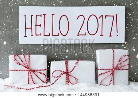 Three Christmas Presents On Snow. Cement Wall As Background With Snowflakes. Modern And Urban Style. Card For Birthday Or Seasons Greetings. Label With English Text Hello 2017 For Happy New Year