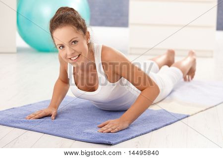 Pretty young girl doing exercises on floor at home, smiling.?