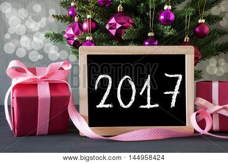 Christmas Tree With Rose Quartz Balls And Bokeh Effect. Gifts Or Presents In The Front Of Cement Background. Chalkboard With English Text 2017 For Happy New Year