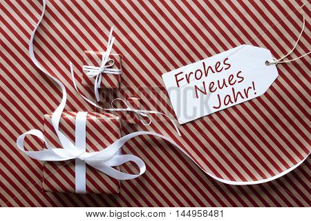 Two Gifts Or Presents With White Ribbon. Red And Brown Striped Wrapping Paper. Christmas Or Greeting Card. Label With German Text Frohes Neues Jahr Means Happy New Year