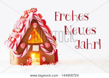 Gingerbread House In Snowy Scenery As Christmas Decoration With White Background. Candlelight For Romantic Atmosphere. German Text Frohes Neues Jahr Means Happy New Year