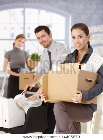 Happy businesspeople moving to new office, packing boxes, smiling.?