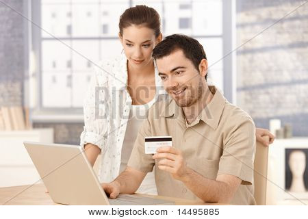 Happy Couple using Laptop, online-shopping zu Hause, Kreditkarte verwenden.?