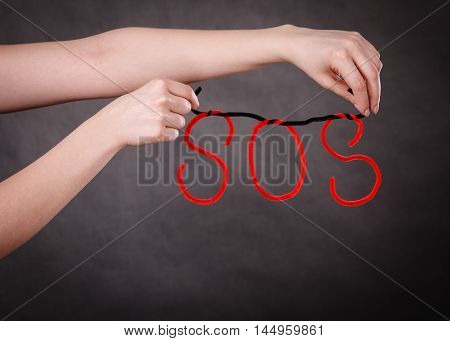 Sadness and depression concept. Woman hands with big red sos word on dark background. Girl in troubles needs help.