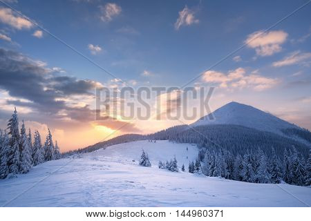 Winter landscape with a road in the mountains. Sunrise with beautiful clouds. The top and the field. Carpathians, Ukraine, Europe