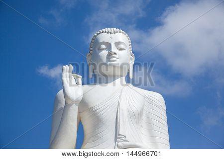 White Buddha statue in monastery. Mihintale Sri Lanka