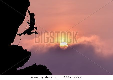 Silhouette of rock climber over nightly sky with moon
