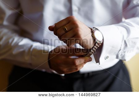 Hours on hands. Businessman looking at his watch in office