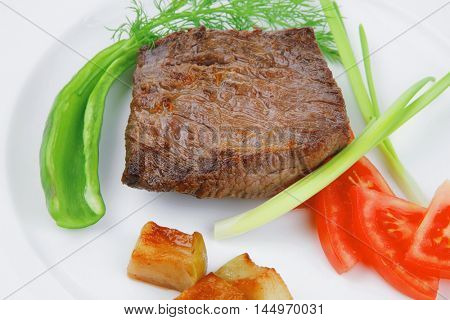 meat food : roast beef fillet mignon served on white plate with apples dill and tomatoes isolated over white background