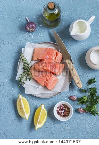 Cooking healthy lunch - raw salmon lemon olive oil spices and herbs on a blue background. Top view