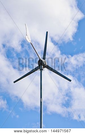 Wind electric turbine. View from below of a windmill for electric power production alternative energy resources renewable energy sources. Outdoor with bright sunlight at daytime.