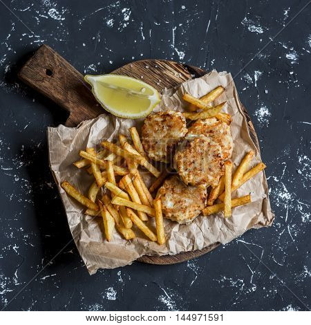 Fish balls and potato chips on rustic cutting board on a dark background. Top view
