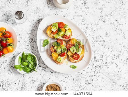 Bruschetta with cherry tomatoes avocado and basil. On a light background. Healthy snack