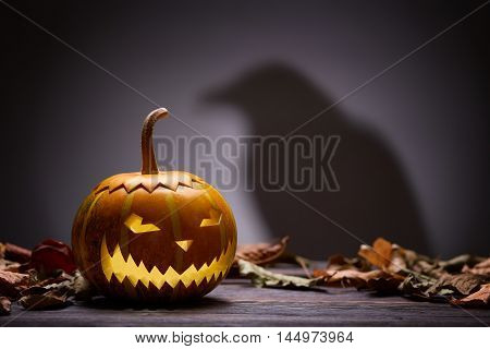 Pumpkin for Halloween, lamp pumpkin, crow silhouette, antique wood, celebrating halloween, smiley on a pumpkin, bright background, autumn dry leaves