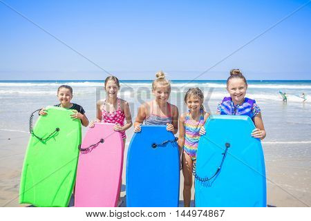 Group of cute kids standing by their boogie boards at the beach while playing in the ocean