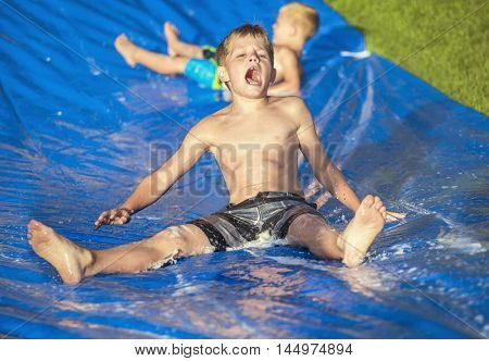 Excited little boys playing on a slip and slide outdoors