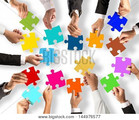 Business people join the colorful puzzle pieces. Concept of teamwork and integration
