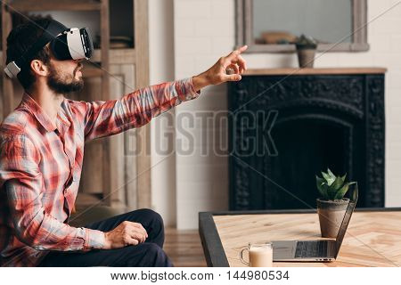 Serious man choosing something in vr glasses. Bearded guy in virtual reality headset touching invisible screen. Modern technology, innovation, cyberspace, entertainment concept