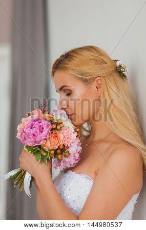 Portrait of a beautiful blonde bride with bouquet, wedding concept