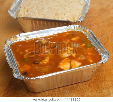 Chinese chicken curry & egg fried rice in takeaway foil containers.