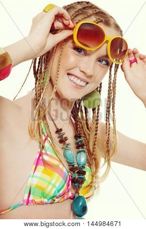 Vintage style shot of young beautiful blond laughing girl with fancy hairstyle, ethnic necklace and sunglasses